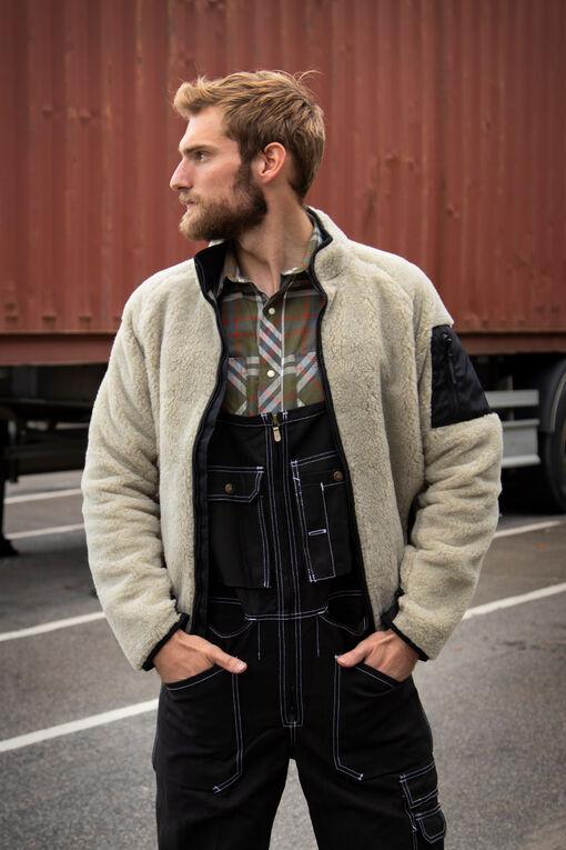 Man met Amerikaanse overall, flanellen overhemd en teddyjack