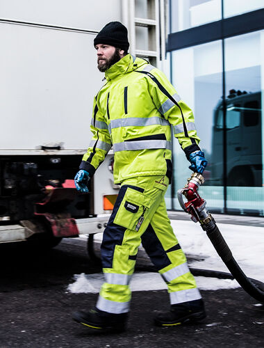 man bij vrachtwagen in vlamvertragende werkkleding