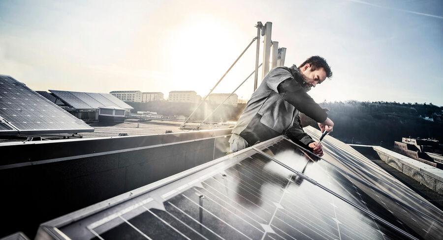 In ecologische werkkleding voor de bouw installeert deze man zonnepanelen - Fristads Green collectie