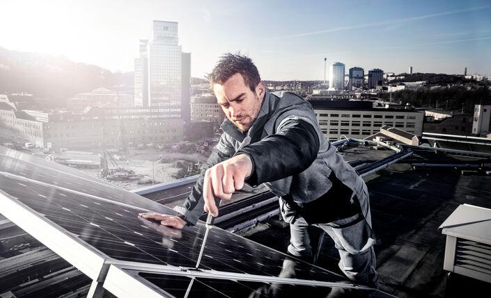 Man in Fristads Green monteert een zonnepaneel