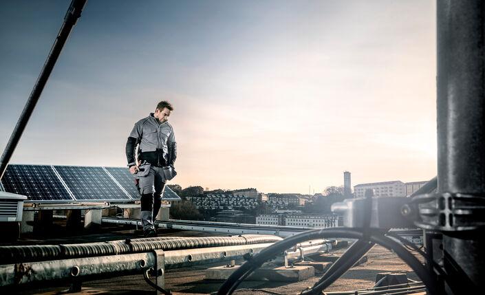 Fristads Green gedragen door een man op een dak met zonnepanelen