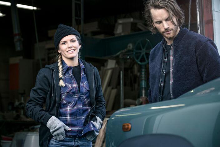 Man en vrouw in werkkleding bij een auto