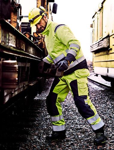 Man aan het werk aan een trein in vlamvertragende werkkleding